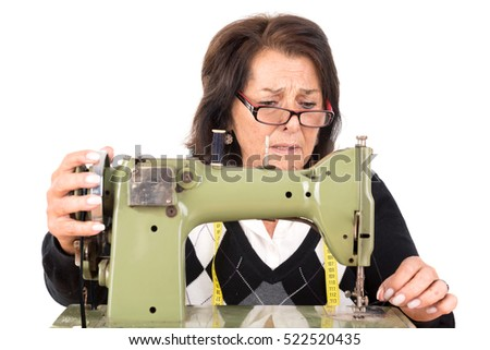 Beautiful senior woman with sewing machine isolated in white