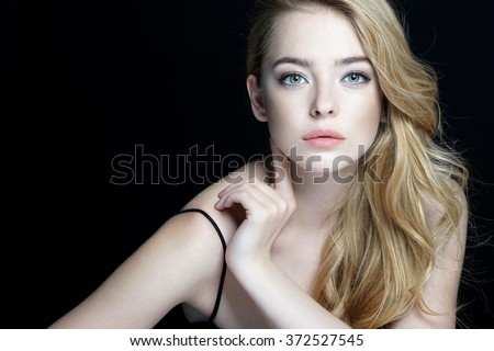 Beautiful sensual blonde girl. Close-up of an attractive girl of European appearance on dark background. - stock photo