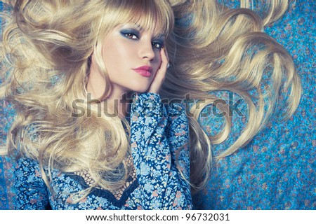 Beautiful sensual blonde lying on a blue pattern - stock photo