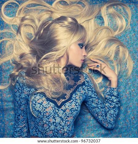 tóc vàng gợi cảm xinh đẹp nằm trên một mô hình màu xanh