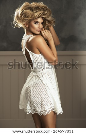 Beautiful sensual blonde woman with long curly hair in white dress. Beauty photo.  - stock photo