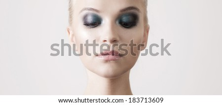 Beautiful sensual blonde woman with perfect makeup and closed eyes posing in studio. Beauty portrait. - stock photo