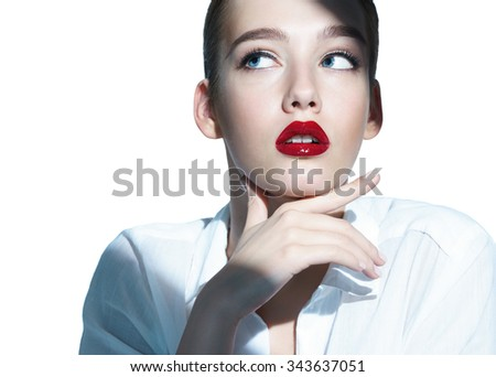 Beautiful sensual brunette girl with red lips looking up / close-up of an attractive girl of the European appearance in a white shirt - isolated on white background - stock photo