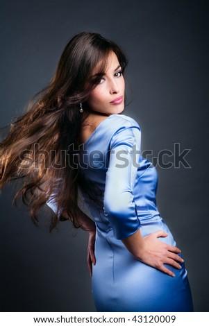 beautiful sensual brunette in motion in blue shiny dress, studio shot - stock photo