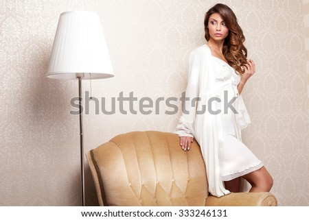 Beautiful sensual brunette woman posing in elegant room in nightwear.  - stock photo