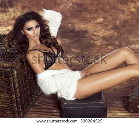 Beautiful sensual brunette woman posing in fashionable lace lingerie. Attractive girl with long slim legs, perfect body. Girl looking at camera. - stock photo
