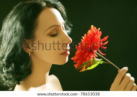 Beautiful sensual expressive brunette woman with red flower on black background.