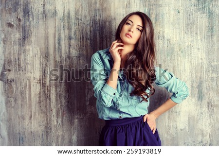 Beautiful sensual woman in jeans clothes stands by the grunge wall. Fashion. - stock photo