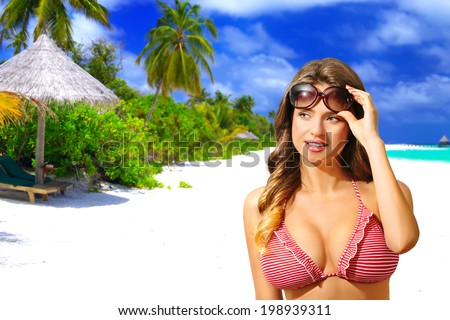 Beautiful sensual woman with bikini and sunglasses, on the white sandy beach, Maldives. Half body portrait, long curly blond hair - stock photo
