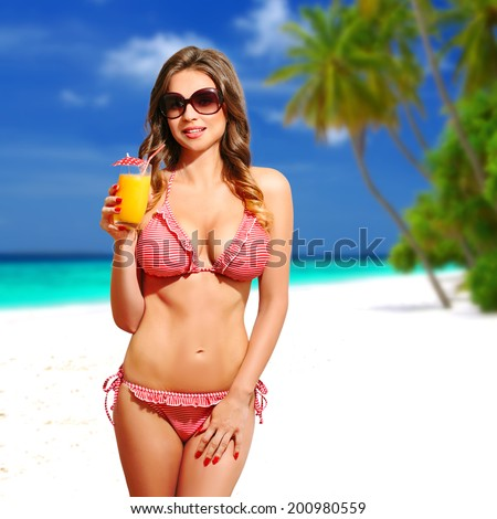 Beautiful sensual woman with bikini, sunglasses and cocktail, on the white sandy beach, Maldives. Half body portrait, long curly blond hair, fashion portrait - stock photo