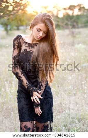 Beautiful sensual woman with dark hair and tanned body,wearing elegant clothes,posing in summer field at sunset - stock photo