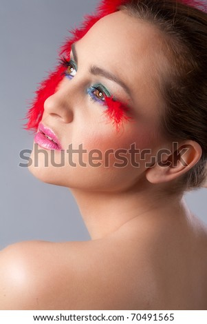 Beautiful, sensual woman with fashion make up and face surrounded by feathers. Fashion style portrait. - stock photo