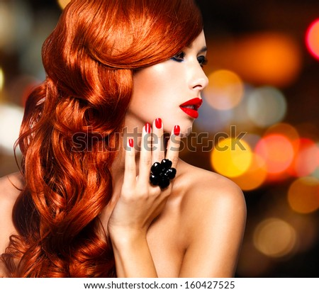 Beautiful sensual woman with long red hairs and red nails -   over art blink night lights - stock photo