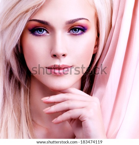 Beautiful sensual woman with pink silk touching her face  isolated on white. - stock photo