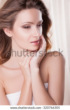 Beautiful sensual young woman with clean fresh skin. Attractive woman with blond hair developing on her head. Youth and beauty. The concept of beauty care, make-up, facials and body treatments. - stock photo