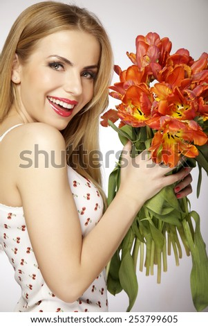 Beautiful sensuality and attractive sexy smiling spring blonde young adult girl with the bouquet of red and yellow tulips flowers isolated on a white background - stock photo