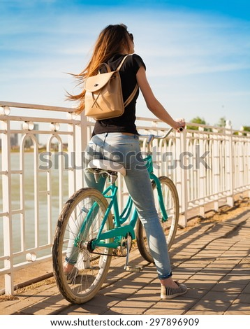 beautiful sensuality elegance brown hair back woman happy fun blue sky black t-shirt jeans bicycle urban city portrait nature slim sport body hobby equipment riding bike cyclist  - stock photo