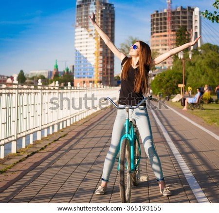 Beautiful sensuality elegance brown hair woman cyclist, has happy fun cheerful smiling face, black  t-shirt, blue jeans. Has slim sport body. Motion on great bicycle in urban city. Portrait nature.  - stock photo