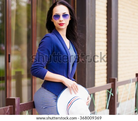 Beautiful sensuality elegance brunette hair woman, has happy fun cheerful smiling face, blue sunglasses, sexy slim body, striped dress, blue jacket. Portrait urban city. Sunny day. - stock photo