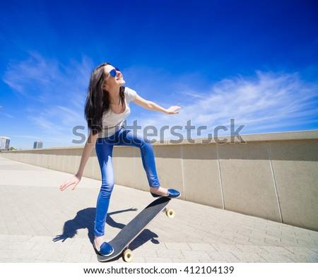 Beautiful sensuality elegance brunette hair woman, has happy fun cheerful smiling face, white t-shirt, blue jeans, long legs, holding skateboard. Has slim sport body. Portrait urban city.  - stock photo