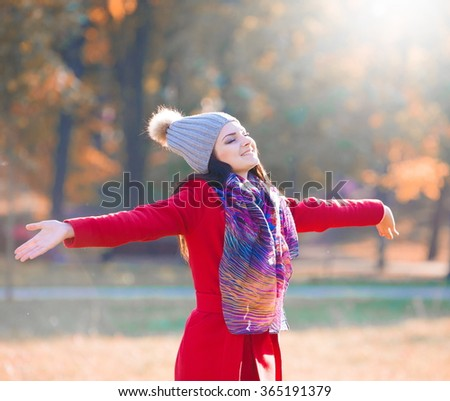 Beautiful sensuality elegance brunette woman, has happy fun cheerful smiling face, brown eyes, red coat and gray knitted hat, scarf, sexy lips. Portrait nature. Sunny day. Classic style - stock photo
