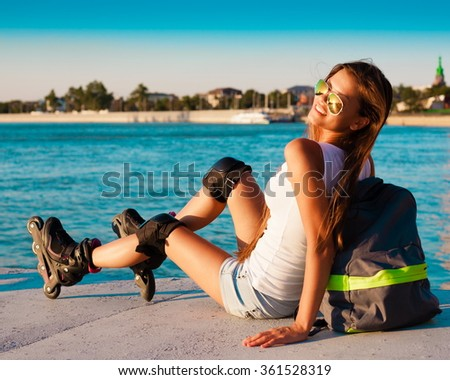 Beautiful sensuality elegance brunette woman, has happy fun cheerful smiling face, white t-shirt, blue jeans shorts, slim sport tan body. Motion on great rollerblading urban city. Portrait nature.  - stock photo