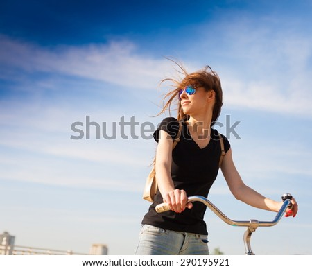 beautiful sensuality elegance haired hair woman happy fun cheerful smiling blue sunglasses black t-shirt jeans bicycle urban city portrait nature slim sport body hobby equipment riding bike cyclist  - stock photo