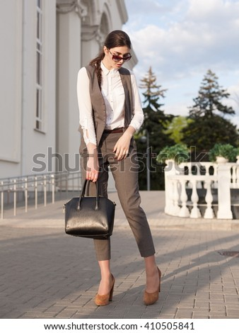 Beautiful sensuality elegance lady brunette woman, has cute face, dressed in gray business suit, white blouse, sunglasses, holding black leather handbag. Urban city portrait. Lifestyle background