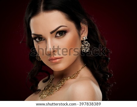 Beautiful sensuality elegance lady face woman, has brown eyes, long eyelashes, brunette hair, sexy lips, necklace and earrings. Studio portrait.  Gold makeup. Red background.