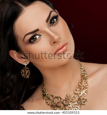 Beautiful sensuality elegance lady face woman, has brown eyes, long eyelashes, brunette hair, sexy lips, necklace and earrings. Studio portrait.  Gold makeup. Red background. Close up.