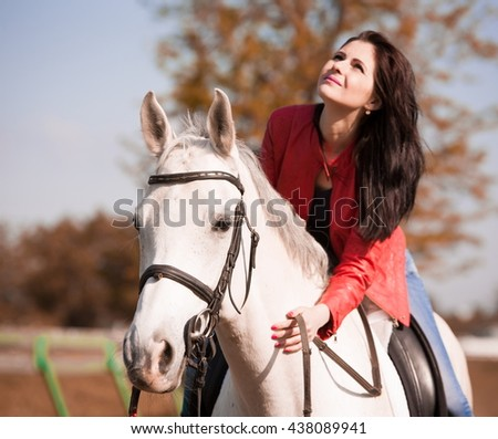 Beautiful sensuality elegance woman cowgirl, riding a white horse. Clothed blue jeans, red leather jacket. Has slim sport body. Portrait nature. People and animals. Equestrian. American ranch. - stock photo