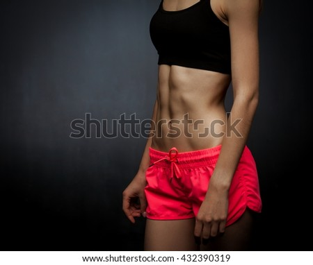 Beautiful sensuality elegance woman, has sport athletic body, slim hips, relief stomach, thin waist, clothed in pink shorts and bra. Portrait studio. Black background. Close up.
