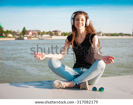 Beautiful sensuality haired woman, has happy fun cheerful smile, slim body, black t-shirt, blue jeans, music headphones. River nature city. Urban portrait. Sunny sky. Bright day. Meditation. - stock photo