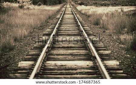 Beautiful sepia colored railroad tracks fading in horizon - stock photo