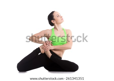 Beautiful serene girl doing stretching exercises, sitting in yoga pose Dedicated to the Sage Vamadeva, Vamadevasana - stock photo