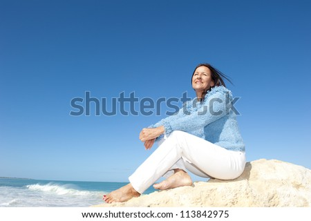 Beautiful serene senior woman enjoying active retirement, sitting relaxed at beach, isolated with ocean and blue sky as background and copy space. - stock photo
