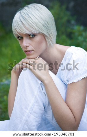 Beautiful serene young blond woman sitting enjoying the freedom of nature resting her chin on her knee looking sideways at the camera with a calm expression - stock photo