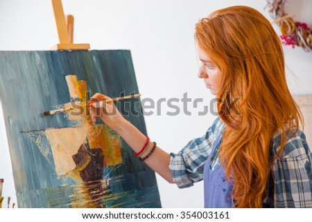 Beautiful serene young female painter with long red hair painting picture on canvas in art workshop - stock photo