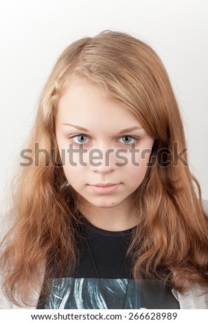Beautiful serious blond Caucasian girl in black, close up studio portrait - stock photo