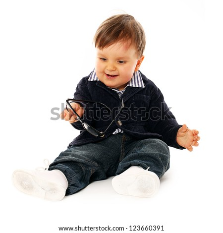 Beautiful serious little boy in a coat and jeans  isolated over white background