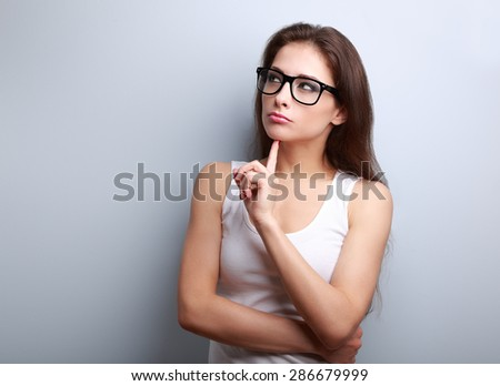 Beautiful serious thinking young woman looking up on empty copy space - stock photo