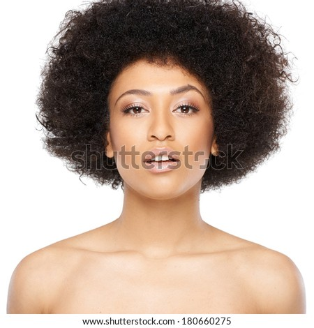 Beautiful serious young African American woman with bare shoulders looking at the camera with her head tilted and a serious expression, isolated on white - stock photo
