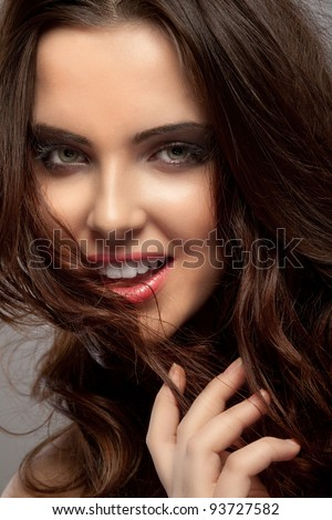 Beautiful serious young girl with brown hair in a bob on grey background - stock photo