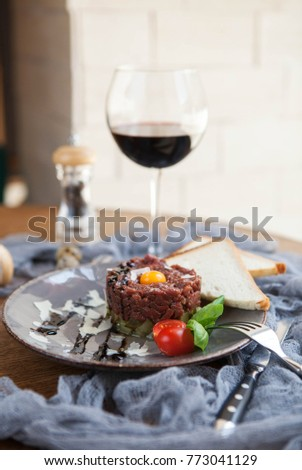 beautiful serving of beef tartare with quail egg yolk with two slices of bread and a glass of wine on a gray plate