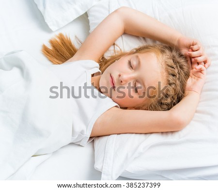 Beautiful seven year old girl sleeping in white bed