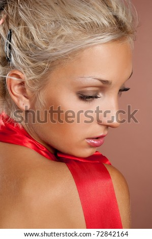 Beautiful sexual girl blonde in bright color gown for summer on brown background