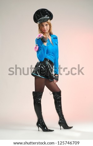 Beautiful sexual girl in carnival suit police on light pink background