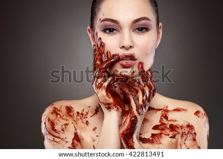 Beautiful sexual  girl with green eyes in a molten chocolate - stock photo