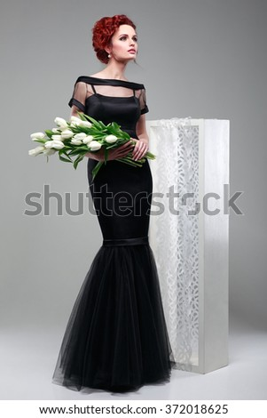 Beautiful sexual redheaded girl in evening dress   with a bouquet of white tulips on a gray background - stock photo