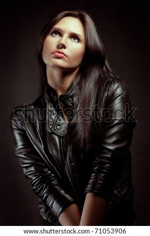 beautiful sexual  woman portrait wearing leather jacket near wall - stock photo
